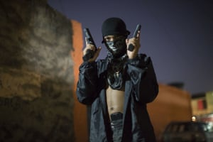A young, masked drug trafficker poses for photos in Rio de Janeiro