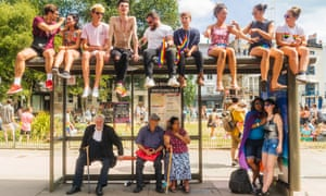 Young and old people wait for a bus after Brighton's Pride parade