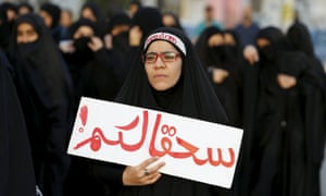 """Protester holds a banner saying """"to hell with you"""" as she takes part in a protest against the execution of Saudi Shia cleric Nimr al-Nimr by Saudi authorities, in the village of Sanabis.<br>"""