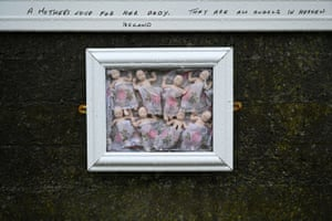 "Eight baby dolls in a frame with ""A mother's love for her baby. They are all angels in heaven. Ireland"" handwritten above it"