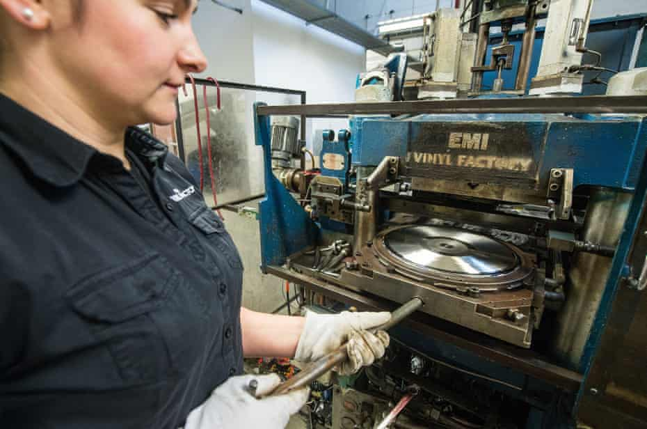 Factory worker Aga Dolega-Lawry places a master record into a pressing machine to make copies of Definitely Maybe by Oasis at The Vinyl Factory in Hayes, UK.