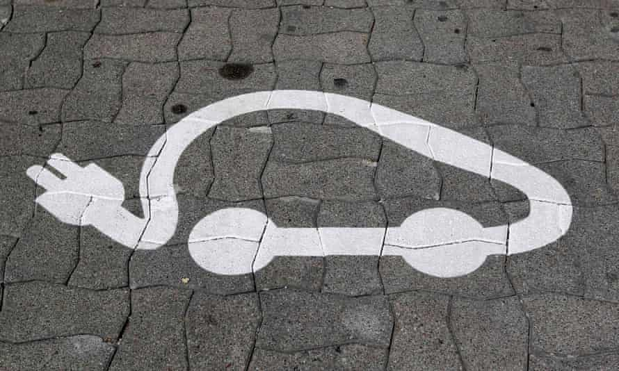 The pictogram of an electric car is painted on a parking space