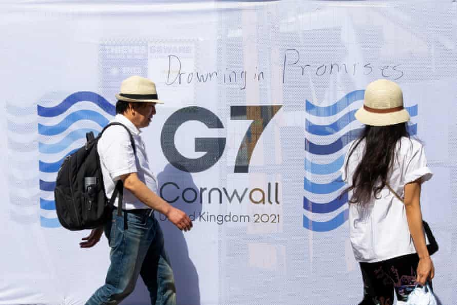 People walk past a sign saying 'Drowning in Promises' written near the media centre in Falmouth
