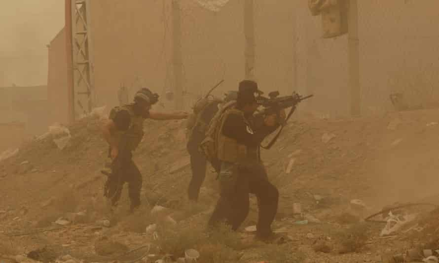 In this 14 May 2015 file photo, security forces defend their headquarters against attacks by Isis during a sand storm in the eastern part of Ramadi. The city fell to Isis forces three days later.