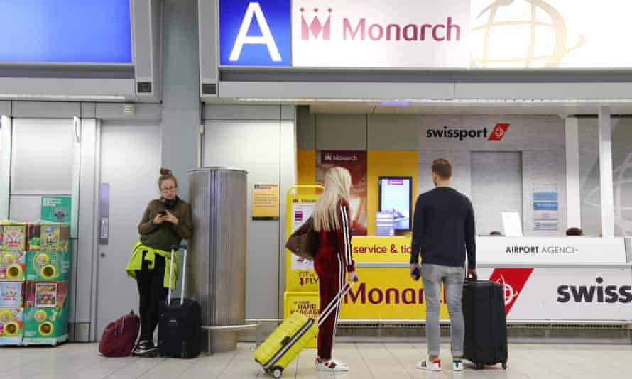 Would-be passengers stand at an empty Monarch service desk at the Luton airport