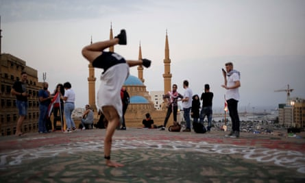 Young people socialise on a roof with Beirut's Mohammad Al-Amin mosque in the background, November 2019.