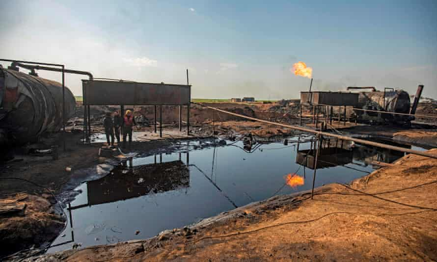Men work at a primitive oil refinery in the countryside of al-Qahtaniyah town, in Syria's north-eastern Hasakeh province