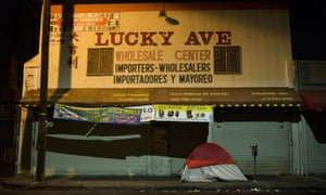 A homeless person's tent is pitched on a sidewalk in front of the wholesale store Lucky Ave, in downtown Los Angeles.