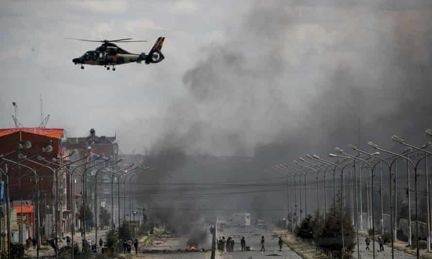 An army helicopter flies over the road leading to the state-own Senkata filling gas plant in El Alto, on the outskirts of La Paz, Bolivia, as supporters of former President Evo Morales set up barricades on Tuesday.