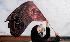 An Extinction Rebellion activist holds a flag with their symbol during a protest at the Gendarmenmarkt square in Berlin on April 27, 2019