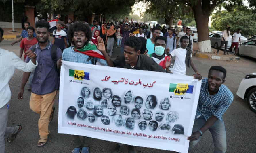 Demonstrators hold a banner bearing images of protesters allegedly killed in unrest in Khartoum in June 2019