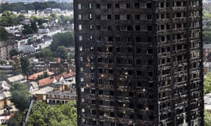 Firemen examine the scorched facade of the Grenfell Tower in London