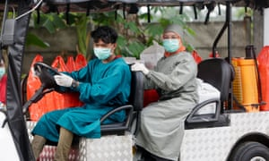 Healthcare workers on a golf cart carry food for patients in isolation at The House Against Covid-19 in Tangerang, Indonesia, 02 June 2021.