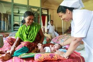 Midwife Parboti Rani Dhali, 45, checks on 8-day-old baby of mother, Shokla Mondol, 19, at Dacope Upazila Health Complex, Chalna, Dacope, Khulna, Bangladesh