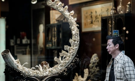 A pedestrian walks past a shop window displaying a carved ivory tusk