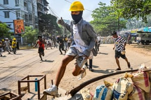 A protester jumps over a makeshift barricade during a crackdown by the security forces in Thaketa township