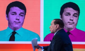 Silvio Berlusconi speaks during a TV programme, with a picture of Matteo Renzi in the background.
