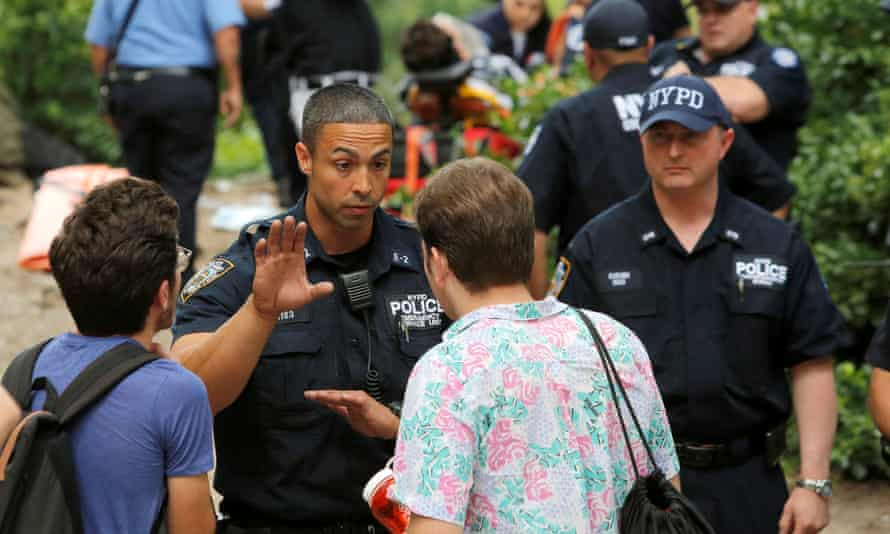 Police speak to people at the scene where a man was injured after an explosion in Central Park on Sunday.