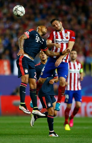 Atletico Madrid's Koke beats Bayern Munich's Arturo Vidal in the air.