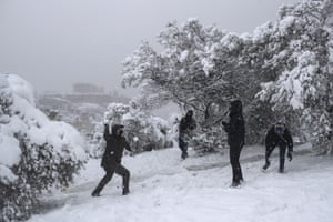 People have a snowball fight in front of the Acropolis.