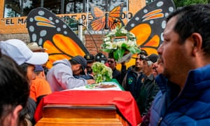 People mourn next to the coffin with the remains of Mexican environmentalist Homero Gomez, during his funeral in El Rosario village, Michoacán, on 30 January.