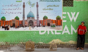 A man with a pair of caged chukars beside a poster depicting the Jamkaran mosque in Iran