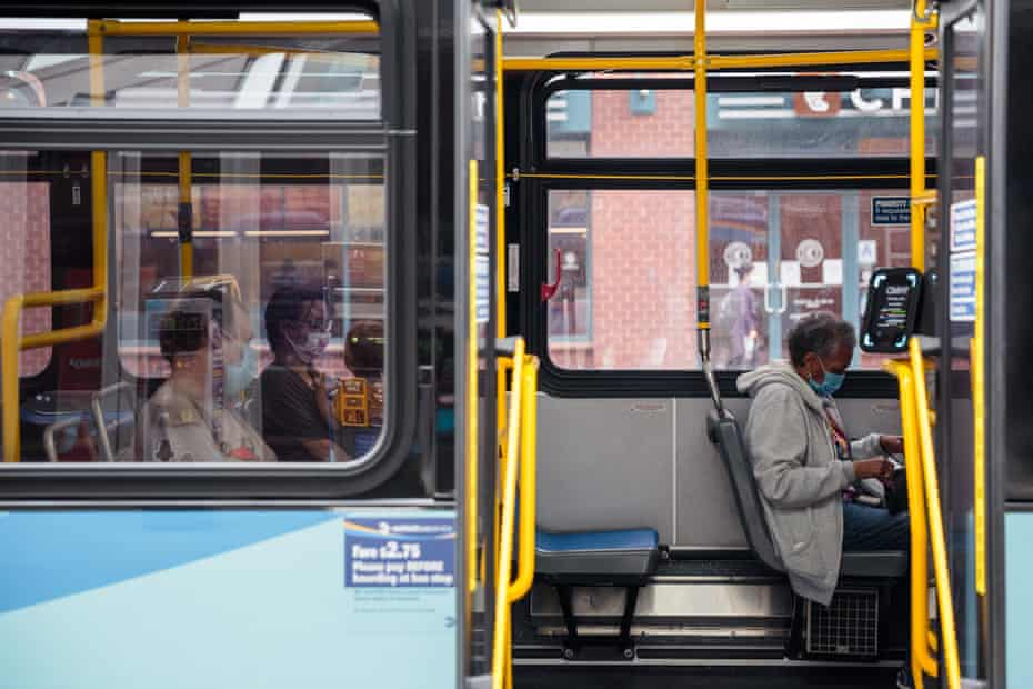 Commuters wearing protective masks sit inside a bus while waiting at the Union Square stop in New York, U.S., on Wednesday, June 3, 2020.