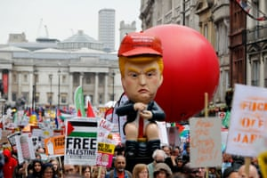 An effigy of President Trump is carried by protestors demonstrating against the visit