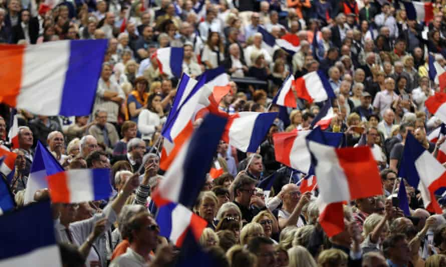 People wave the French national flag during a campaign meeting of presidential election candidate François Fillon, for the right-wing Les Republicains party, on 17 April, in Nice.