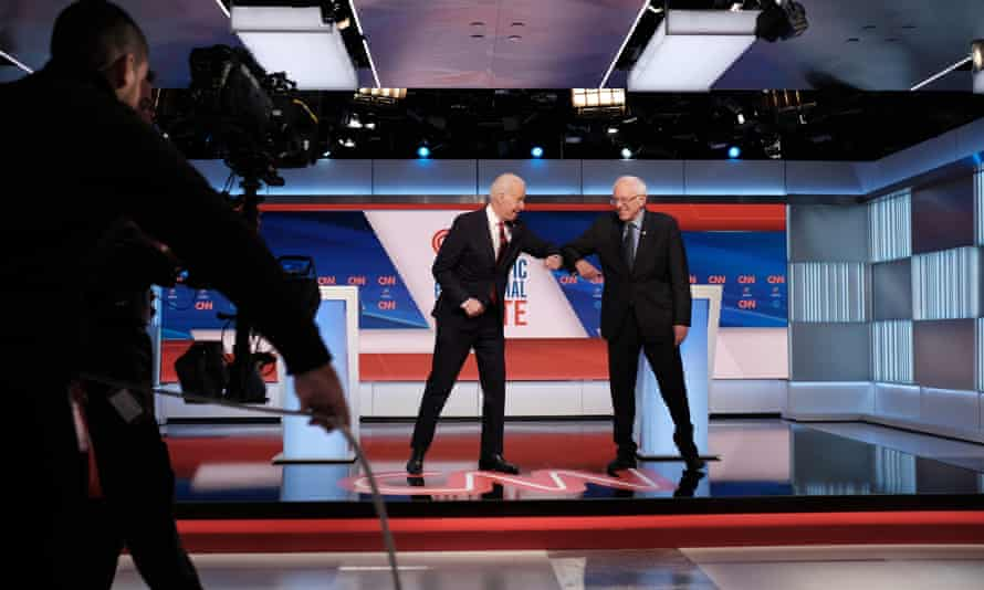 Joe Biden and Bernie Sanders greet each other with their elbows at the last Democratic presidential debate, in Washington. Sanders has been forced to cancel the rallies that are a pillar of his campaign.