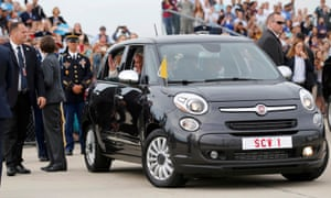 Pope Francis waves as he is driven away in a Fiat 500 model after arriving in the United States at Joint Base Andrews outside Washington on Tuesday.