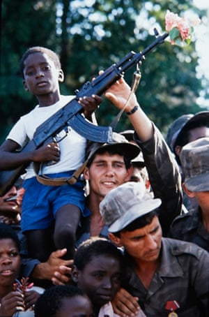 Cuban soldiers with Angolan civilians celebrate at a parade in the capital, Luanda, in 1989, marking the official plan for the withdrawal of Cuban troops from Angola after a UN-brokered peace accord. In the Angolan civil war, the Cubans supported the leftist Soviet-backed MPLA against the anti-communist and US-backed Unita movement.