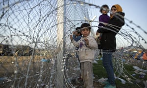 Refugees gather at the barbed wire fence fence at the Greek-Macedonia border in March 2016