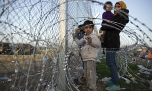 Families gather at the barbed wire fence fence at the Greek-Macedonia border near Idomeni, Greece.