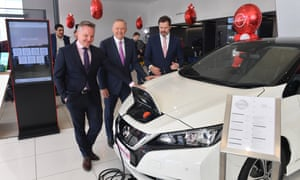 Shadow Minister for Climate Change Chris Bowen, Leader of the Opposition Anthony Albanese and Shadow Minister for Industry Ed Husic with an electric vehicle at a car dealership