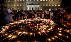 People light candles outside the Greek parliament