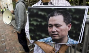 A pro-democracy protester holds a portrait of Chinese human rights lawyer Pu Zhiqiang during a demonstration demanding his release. He was found guilty and given a suspended sentence.