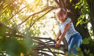 Happy teenage girl climbing tree and smiling.