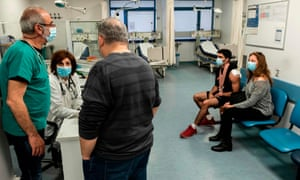 Staff and visitors wearing surgical masks at the Nicosia general hospital in Cyprus. The republic has announced emergency measures, a day after it reported its first two cases of the disease