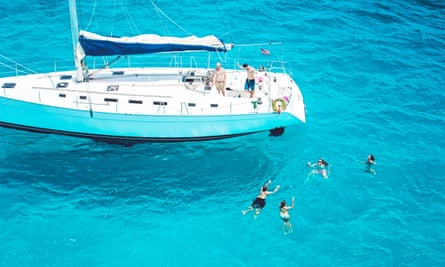 People swimming in turquoise sea next to a yacht