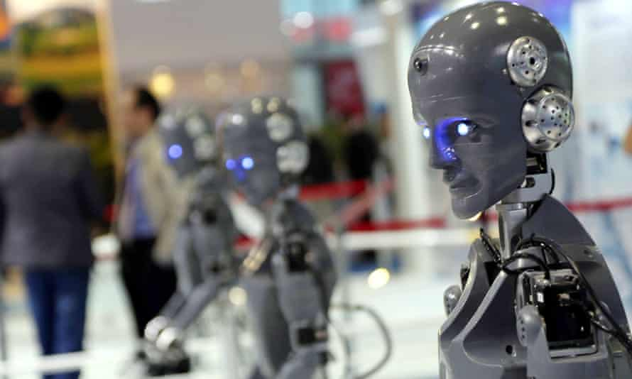 A line of human-shaped robots on display at an industry fair.