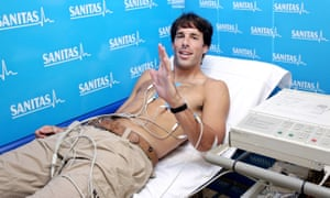 Against a blue advertising background for 'sanitas', Ruud van Nistelrooy lies on a trolley bed, shirtless, with his chest covered in electrodes. A piece of technical equipment sits to the right, and van Nistelrooy is raising his hand and smiling.