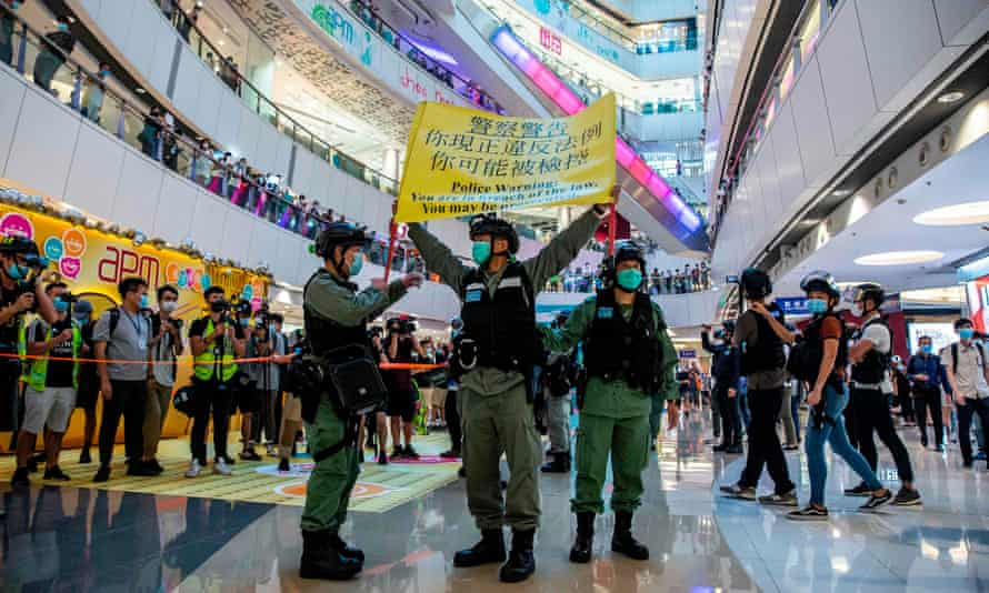 Police wave a warning flag during a pro-democracy protest in a Hong Kong shopping mall on Monday.