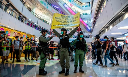 Hong Kong riot police hold up a warning flag during a protest against the new national security laws that have forced the New York Times to move some of its operations to South Korea.