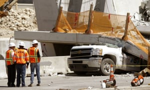 Workers next to a section of a collapsed pedestrian bridge on Friday near Florida International University in the Miami area.