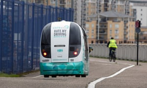 The driverless vehicle travels along the Thames path next to a cyclist.