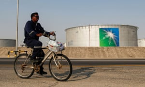 An employee rides a bicycle next to oil tanks at Saudi Aramco oil facility in Abqaiq, Saudi Arabia 12 October, 2019.