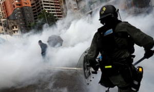 A police officer fires teargas at demonstrators
