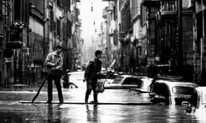 Two men make their way on a makeshift boat through a street in Florence following the flood in 1966.