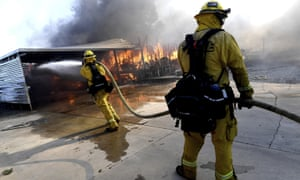 Firefighters try to protect surrounding homes as they battle the Sandalwood fire in Calimesa, California, on 10 October.